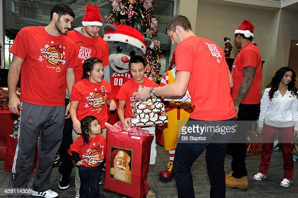 Clutch Mascot Chandler Parsons Omri Casspi Donatas Motiejunas and Greg Smith of the Houston Rockets visit and pass out gifts to children on December...