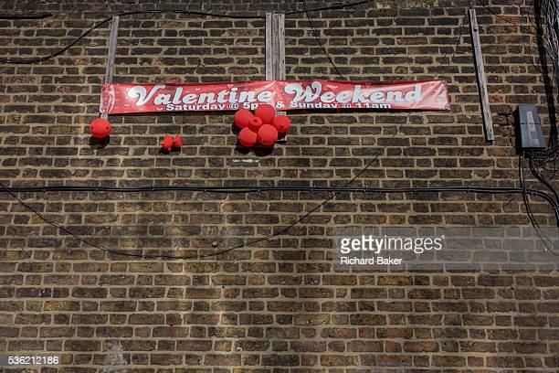 A clutch of deflated red love balloons and a Valentines Weekend banner on a brick wall in south London Looking up we see a detail of the bright reds...