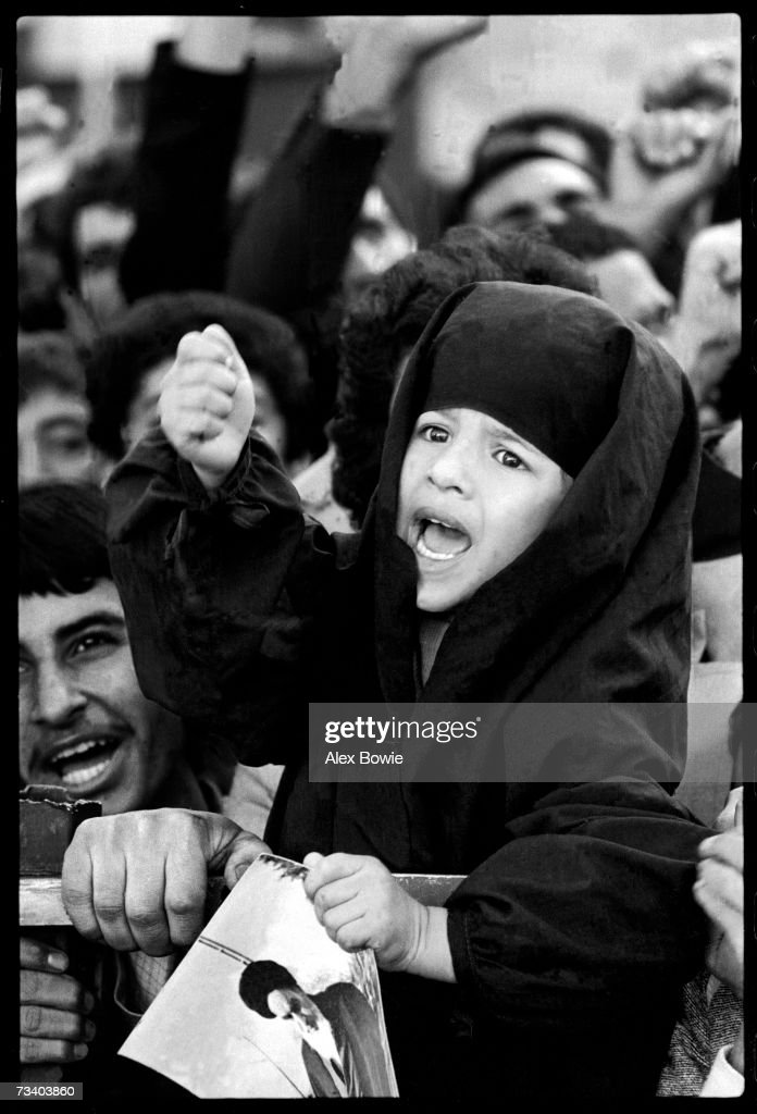 Clutching a picture of the Iranian spiritual leader, the Ayatollah Khomeini, a girl screams 'Death to the Great Satan, Carter. Death to the USA', Teheran, 6th November 1979. Metres away Revolutionary Guards hold 52 US diplomats hostage inside the former US Embassy.
