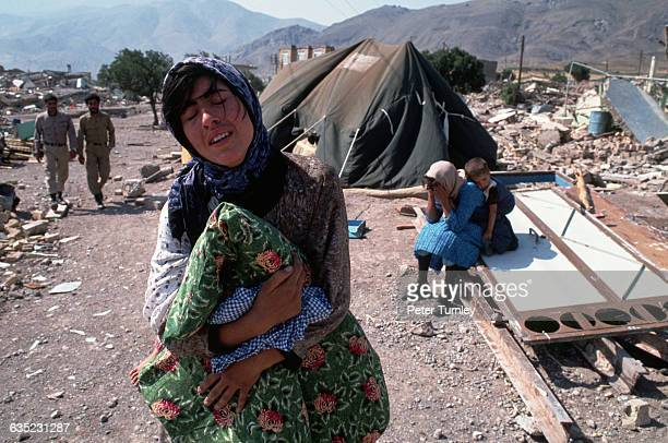 Clutching only a blanket a griefstricken woman wanders through her demolished village after a severe earthquake struck the region Casualty estimates...