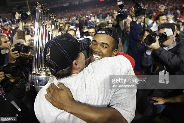 Clutching the trophy Tim Salmon of the Anaheim Angels hugs teammate Garret Anderson after winning World Series game seven against the San Francisco...