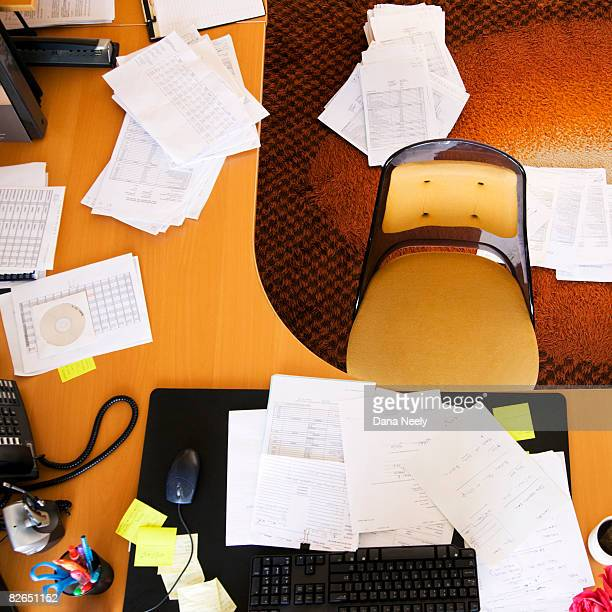 Cluttered desk in office, overhead view