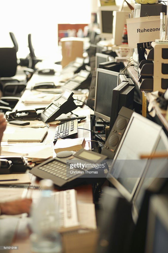 Cluttered workspace in an office : Stock Photo