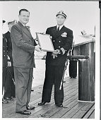 Cmdr Eugene P Wilkinson of San Diego Calif who is to be skipper of the USS Nautilus the world's first atomic powered submarine receives as...