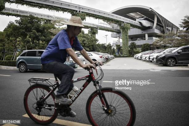 Co SkyRail monorail train stands at a station as an employee rides past on a bicycle at the company's headquarters in Shenzhen China on Thursday Sept...