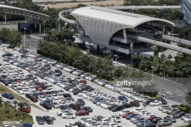 Co SkyRail monorail train stands at a station as vehicles stand parked in a lot at the company's headquarters in Shenzhen China on Thursday Sept 21...