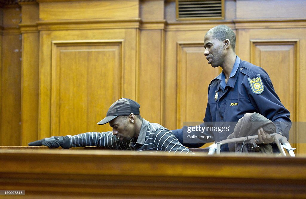 Co-accused Xolile Mngeni is helped to his seat during the murder trial of Anni Dewani, in the Cape Town High Court, on August 30, 2012 in Cape Town, South Africa. Mziwamadoda Qwabe, who has already been convicted of the murder of the honeymooner, today told the court that Mngeni shot Dewani. The deceased's husband Shrien Dewani remains in Britain fighting extradition as he faces accusations of allegedly plotting her murder.