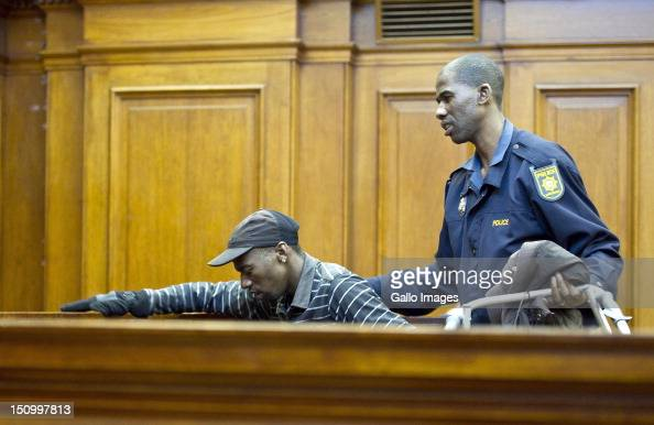 Coaccused Xolile Mngeni is helped to his seat during the murder trial of Anni Dewani in the Cape Town High Court on August 30 2012 in Cape Town South...