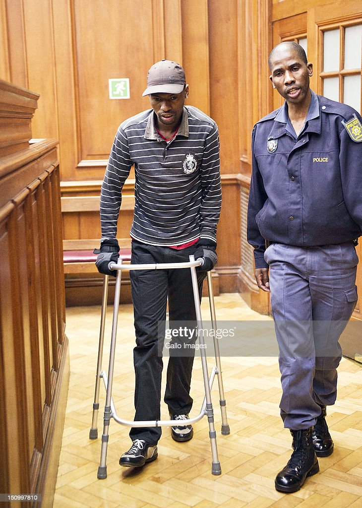 Co-accused Xolile Mngeni uses a zimmer frame as he walks into the murder trial of Anni Dewani, in the Cape Town High Court, on August 30, 2012 in Cape Town, South Africa. Mziwamadoda Qwabe, who has already been convicted of the murder of the honeymooner, today told the court that Mngeni shot Dewani. The deceased's husband Shrien Dewani remains in Britain fighting extradition as he faces accusations of allegedly plotting her murder.