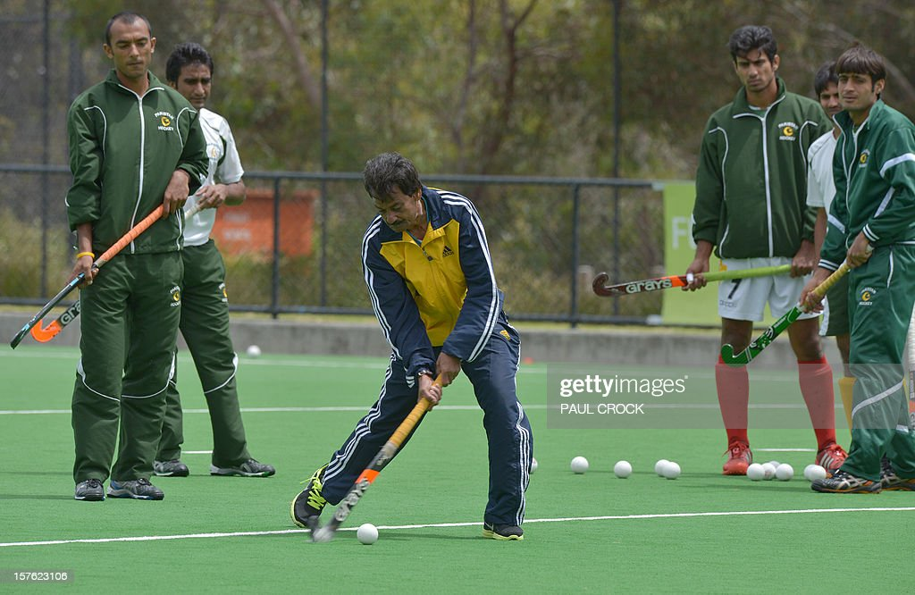 Coach Abdul Haneef Khan of Pakistan (C) demonstrates to players during a practice session at the Men's Hockey Champions Trophy in Melbourne on December 5, 2012. AFP PHOTO/Paul CROCK IMAGE STRICTLY RESTRICTED TO EDITORIAL USE - STRICTLY NO COMMERCIAL USE