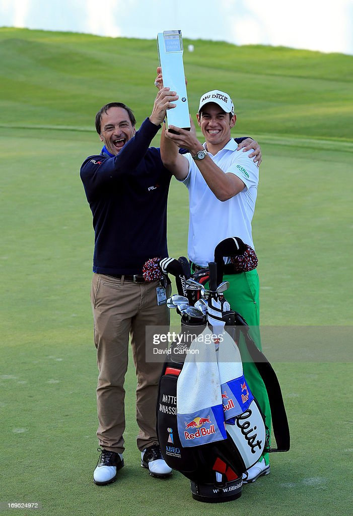 Coach Alberto Binaghi and Matteo Manassero of Italy celebrate with the trophy on the eighteenth green after winning the fourth play-off hole during the final round of the BMW PGA Championship on the West Course at Wentworth on May 26, 2013 in Virginia Water, England.