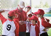 Coach and baseball players (9-11) looking at clipboard in dugout
