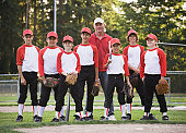 Coach and baseball players (9-14) standing on field, portrait