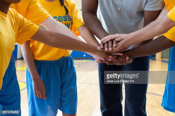 Coach and basketball team putting hands together in huddle