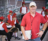 Coach and boys (9-11) in baseball dugout (focus on coach)