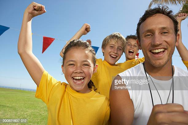 Coach and children's (9-11) soccer team cheering
