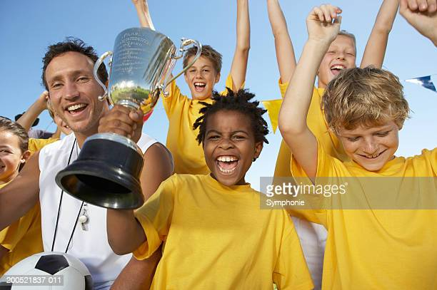 Coach and children's (9-12) soccer team with trophy cheering