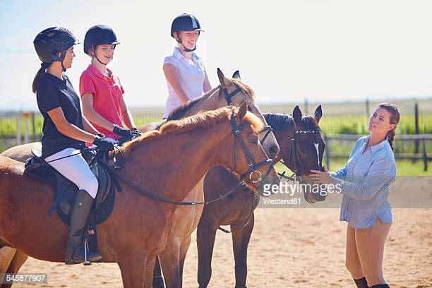 Coach and girls on horses on riding ring