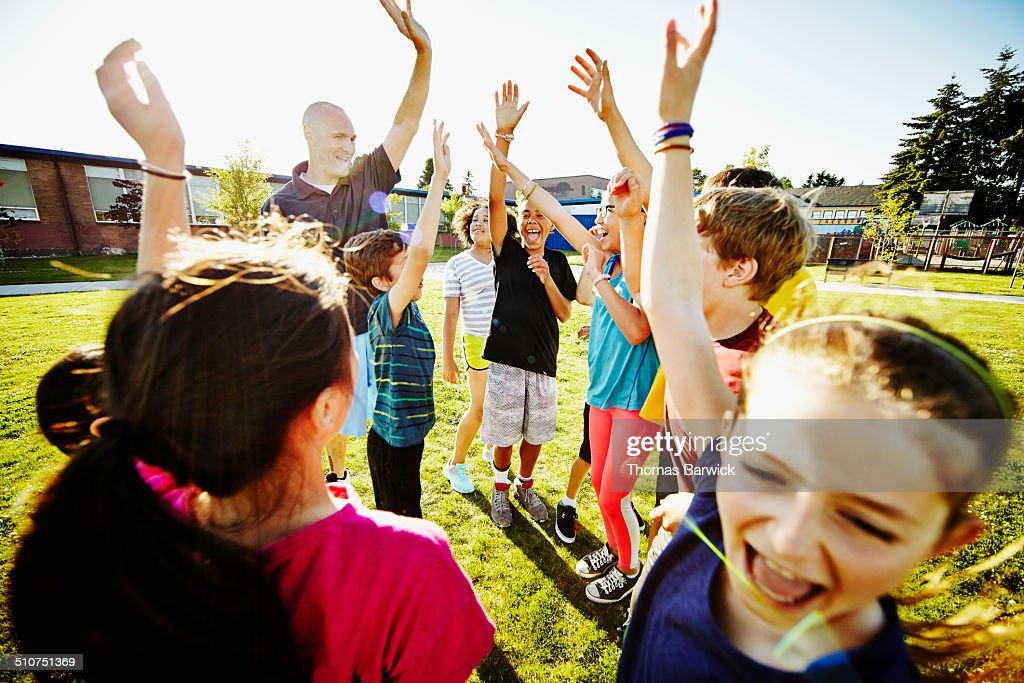 Coach and group of kids cheering after huddle : Stock Photo
