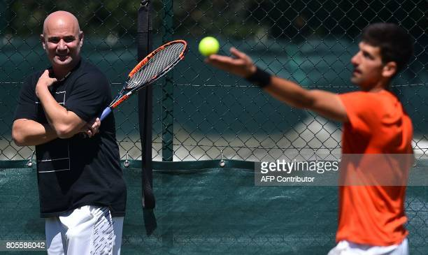US coach Andre Agassi watches Serbia's Novak Djokovic as he attends a practice session at The All England Tennis Club in Wimbledon southwest London...