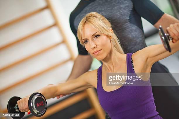 Trainer unterstützen Junge Frau beim Gewichtstraining im Fitnessraum.