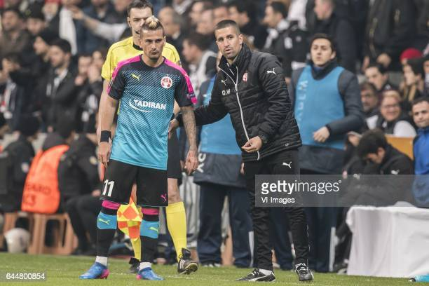 coach Barak Bakhar of Hapoel Beer Sheva give instructions to Maor Buzaglo of Hapoel Beer Shevaduring the UEFA Europa League round of 16 match between...