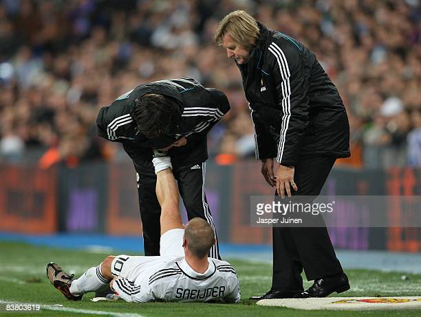 Coach Bernd Schuster of Real Madrid checks on Wesley Sneijder receiving treatment for an injury during the La Liga match between Real Madrid and...