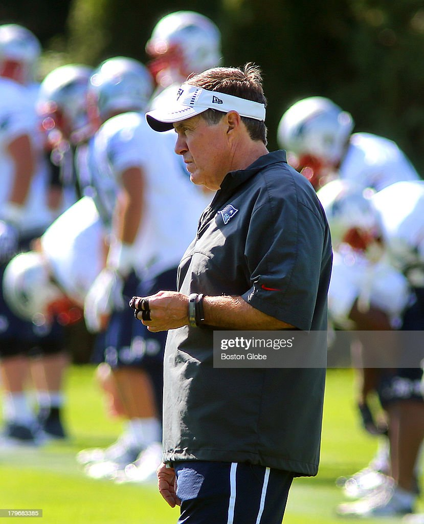 Coach Bill Belichick watches the warmups at the start of practice. The New England Patriots held practice on the practice fields at Gillette Stadium.