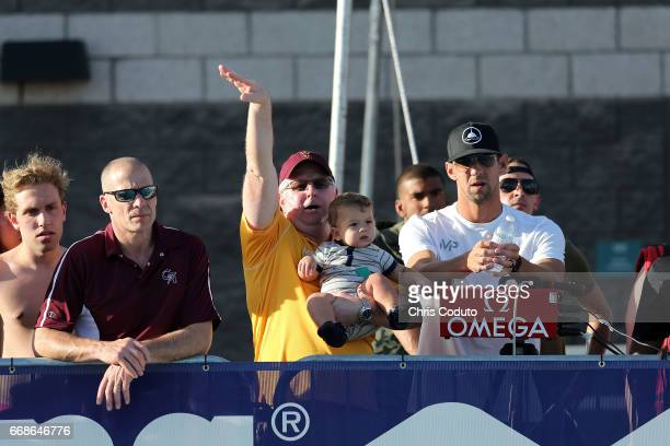 Coach Bob Bowman Michael Phelps and his son Boomer watch the finals of the men's 400 meter individual medley on day two of the Arena Pro Swim Series...