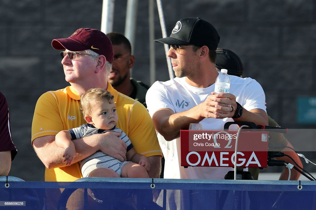 Coach Bob Bowman, Michael Phelps and his son Boomer watch the finals of the men's 400 meter individual medley on day two of the Arena Pro Swim Series - Mesa at Skyline Aquatic Center on April 14, 2017 in Mesa, Arizona.