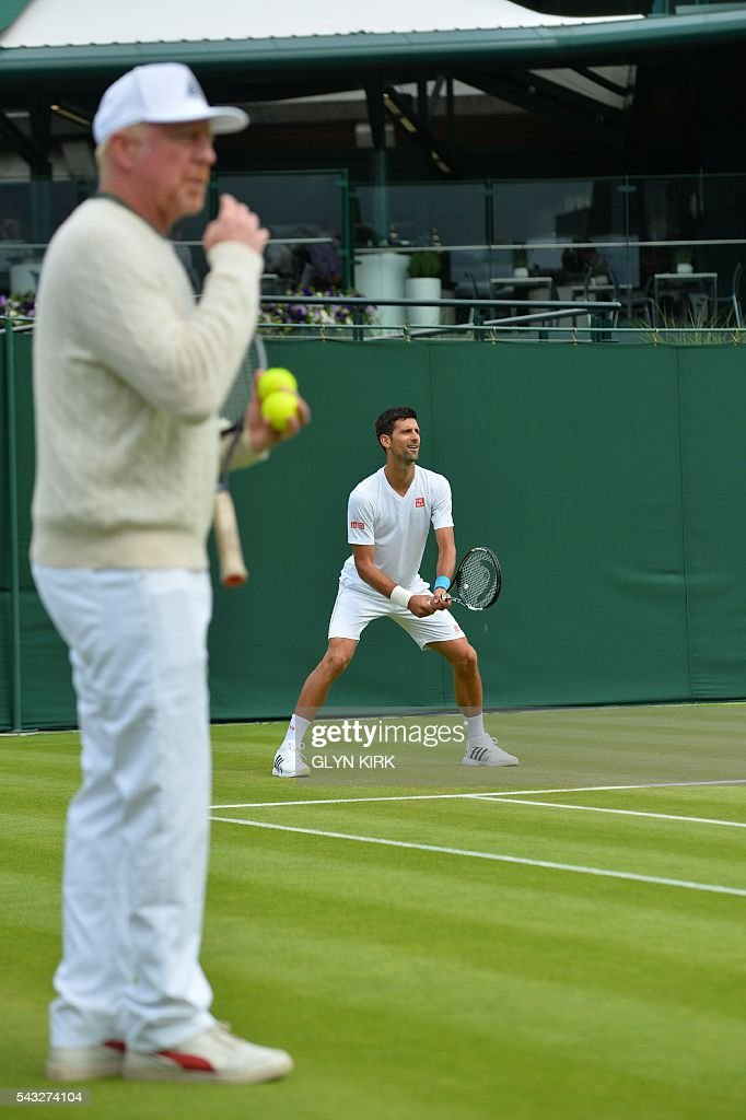 Coach Boris Becker (L) watches as Serbia's Novak Djokovic (R) practices on court 15 ahead of his men's singles first round match against Britain's James Ward on the first day of the 2016 Wimbledon Championships at The All England Lawn Tennis Club in Wimbledon, southwest London, on June 27, 2016. / AFP / GLYN
