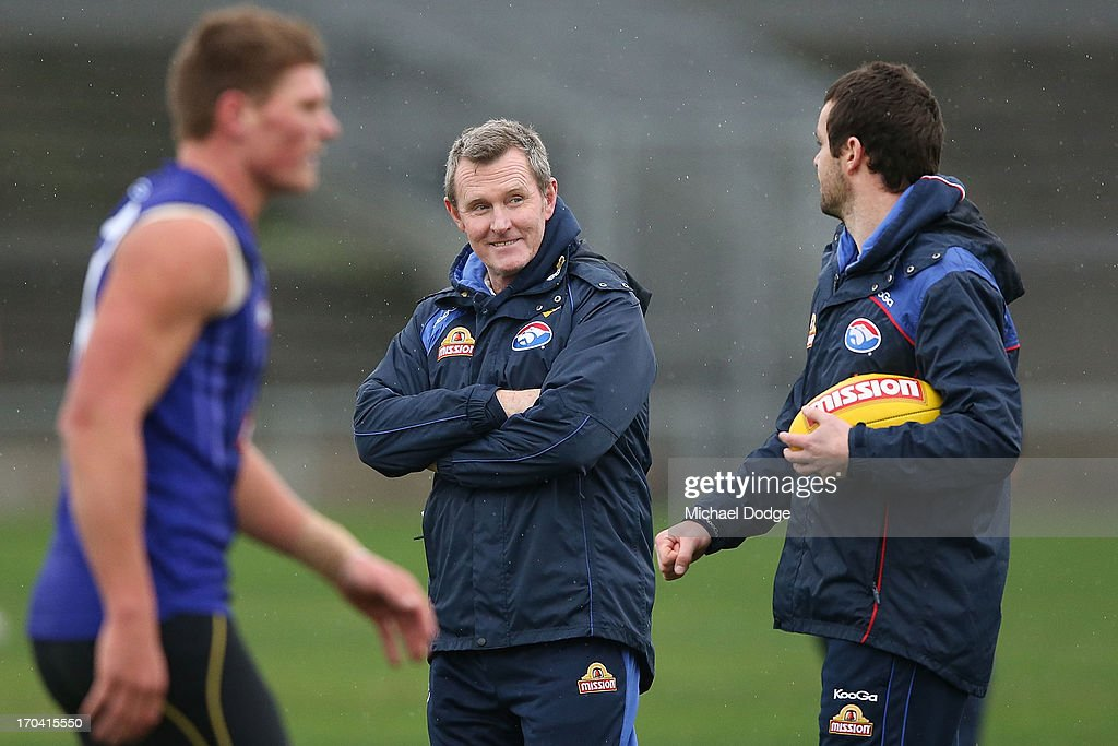 Coach Brendan McCartney (C) reacts to assistant coach Matthew Scarlett during a Western Bulldogs AFL training session at Whitten Oval on June 13, 2013 in Melbourne, Australia.