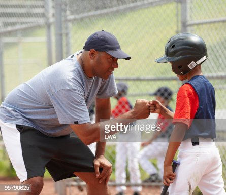 Coach Bumping Fists With Little League Batter