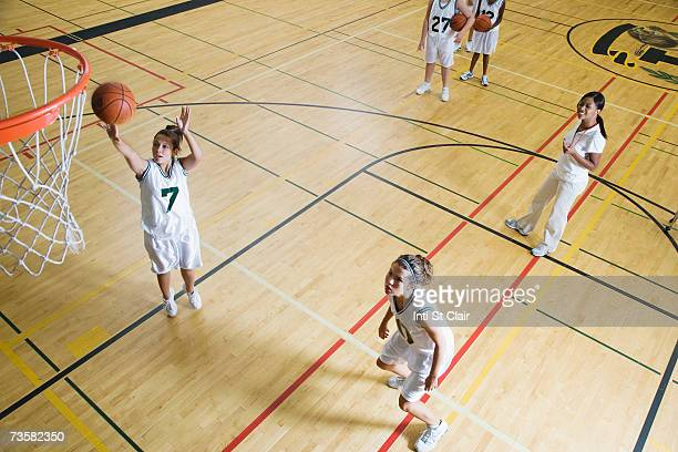 Coach by teenage girls (15-19) playing basketball