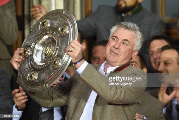 Coach Carlo Ancelotti of Bayern Munich celebrates winning the German soccer championship with the trophy on a balcony of the town hall in Munich...