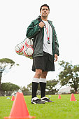 Coach carrying soccer balls on pitch