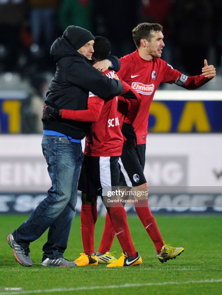 Coach Christian Streich of Freiburg (L) celebrates with Cedrick Makiadi (C) and Julian Schuster the Bundesliga match between SC Freiburg and Fortuna Duesseldorf 1895 at MAGE SOLAR Stadium on February 10, 2013 in Freiburg im Breisgau, Germany.