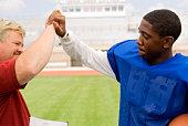 Coach congratulating boy in football gear