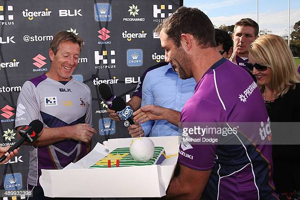 Coach Craig Bellamy reacts as Cameron Smith interupts to present him with a cake to celebrate his 300th game as Storm coach during a Melbourne Storm...