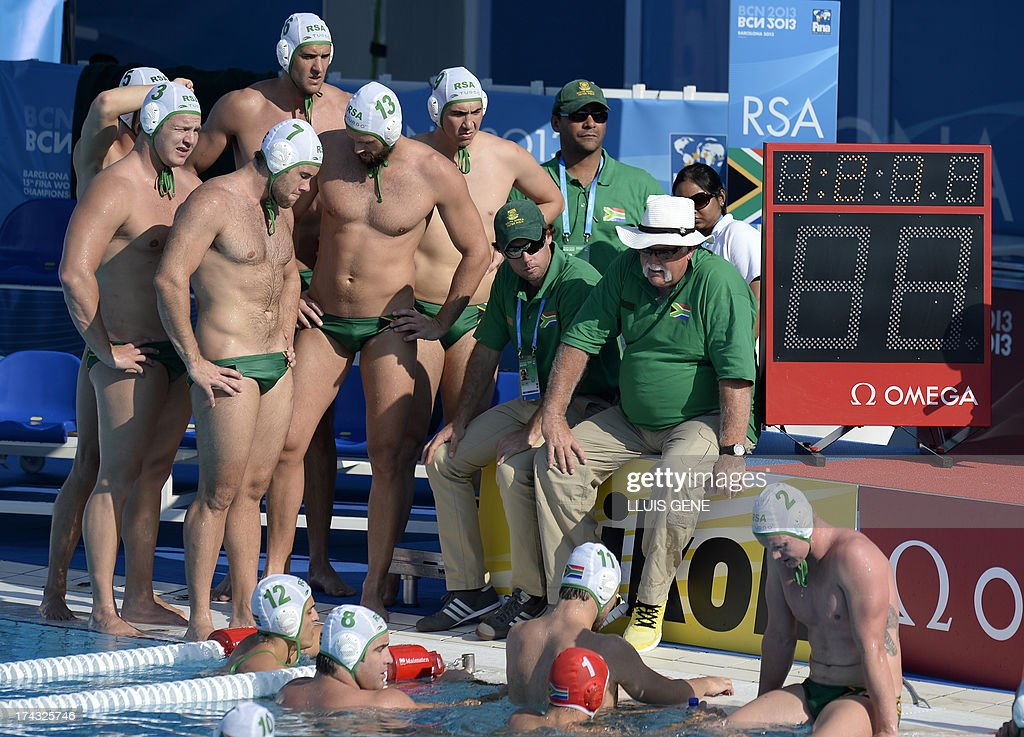 US coach Dejan Udovicic (R) gives instructions to his players during the preliminary round match of the men's water polo competition between the US and South Africa at the FINA World Championships at the Bernat Picornell swimming pool in Barcelona on July 24, 2013. AFP PHOTO/ LLUIS GENE