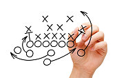 Coach drawing american football or rugby game playbook, tactics and strategy with black marker on white background.