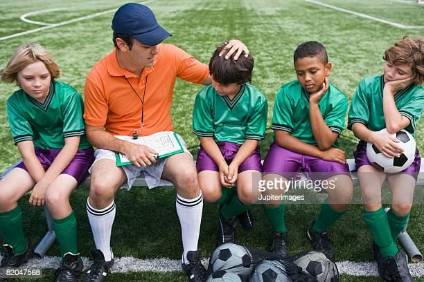 Coach encouraging boys' soccer team