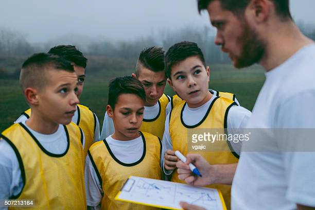 Trainer erklären Strategie zu seinen Kindern Fußball Team