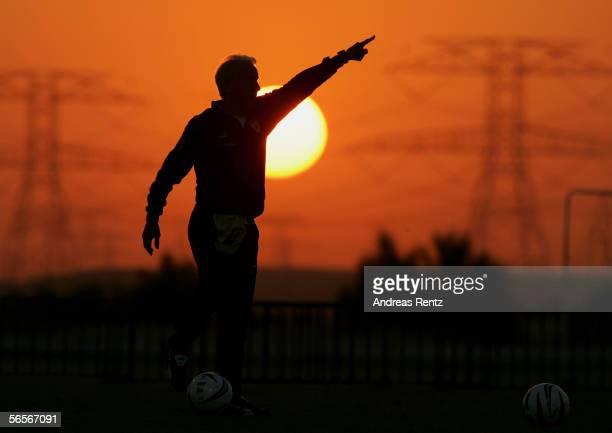 Coach Giovanni Trapattoni gives instructions to the players whilst the sun sets during a training session at the training camp of German Bundesliga...