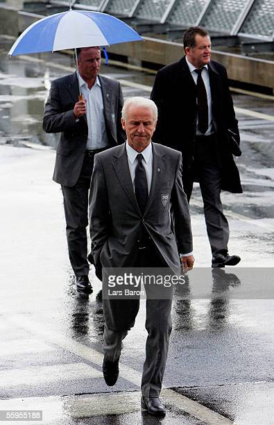 Coach Giovanni Trapattoni walks in the rain in front of Assistant Coach Andreas Brehme and Ulrich Ruf a member of the executive board as VfB...