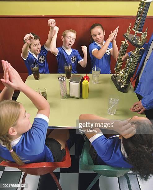 Coach giving trophy to children's (10-12) soccer team in restaurant