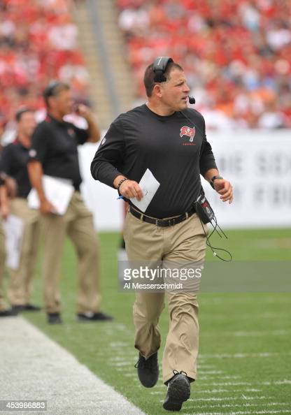 Coach Greg Schiano of the Tampa Bay Buccaneers runs upfield during play against the Atlanta Falcons November 17 2013 at Raymond James Stadium in...