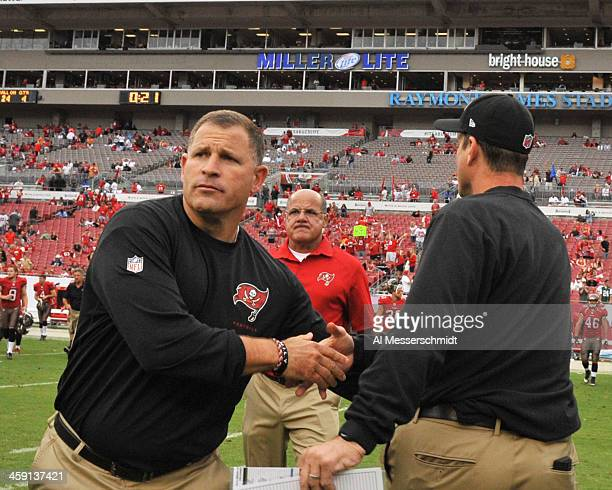 Coach Greg Schiano of the Tampa Bay Buccaneers shakes hands with coach Jim Harbaugh of the San Francisco 49ers after play December15 2013 at Raymond...