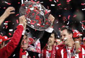 Coach Guus Hiddink holds the plate as PSV Eindhoven won the championship of the Dutch premier soccer league 23 April 2005 in Eindhoven AFP PHOTO...