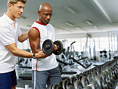 Coach helping a mid adult man exercise with dumbbells